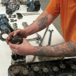 Incarcerated student working with automotive parts